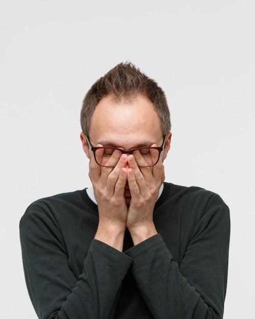 Slaperige man in bril die haar ogen wrijft, voelt zich moe na het werken op de laptop. overwerk, wazige bril, chronische vermoeidheid, mentale stress, gebrek aan slaapconcept Premium Foto