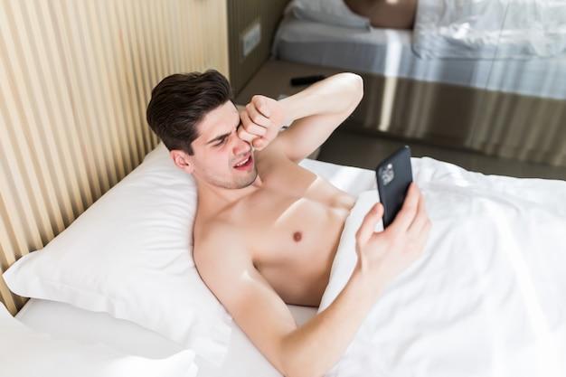 Slaperige mens die in ochtendbed liggen met telefoon die app gebruiken of nieuwsfeed lezen. man wordt wakker van telefoonalarm of telefoontje. Premium Foto