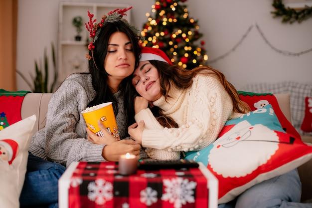 Slaperige mooie jonge meisjes met kerstmuts en hulstkrans houden popcornemmer zittend op fauteuils en genieten van kersttijd thuis Gratis Foto