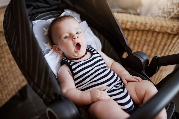 Slaperige schattige kaukasische 6 maanden oude babyjongen zit in de wandelwagen in café en geeuwen. Premium Foto