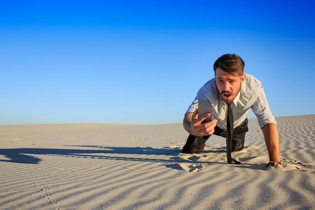 Slecht signaal. zakenman op zoek naar mobiele telefoon signaal in woestijn Gratis Foto