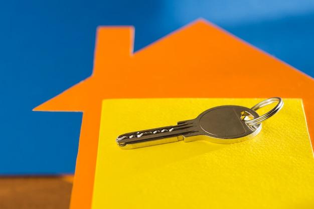 Sleutel voor onroerend goed op de achtergrond van een huis gemaakt van karton Premium Foto
