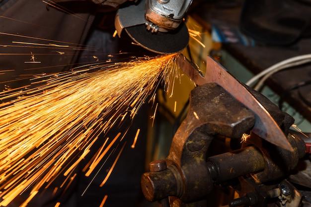 Slijpen van metalen gereedschap met sparkles - smeden werkplaats Premium Foto