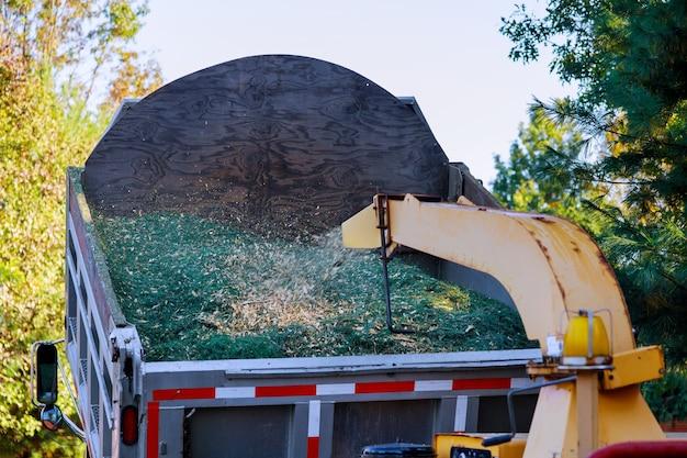 Slijpmachine om tot spaanders gemalen boomtakken te worden voor het mulchen van de grond in de tuin Premium Foto