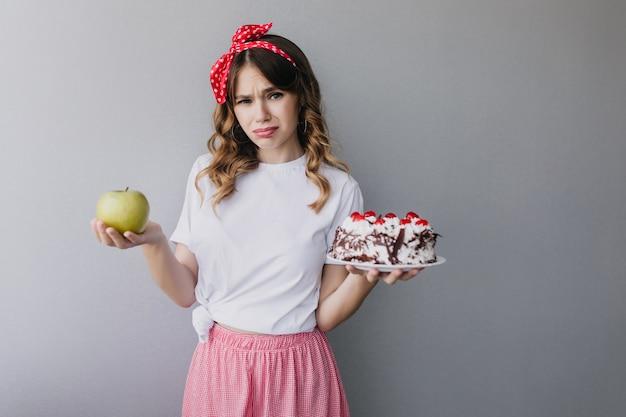 Slim verdrietig meisje met fruit en cake. charmant vrouwelijk model met krullen kan niet beslissen wat te eten. Gratis Foto