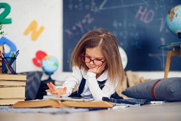 Slim weinig schoolmeisje met digitale tablet in een klaslokaal. Premium Foto
