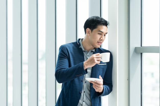 Slimme aziatische zakenman die en koffie in de ochtend bevinden zich dichtbij het venster in hoog de bouwbureau. het portret van de nadenkende zakenman met exemplaarruimte. ondernemers concept. Premium Foto