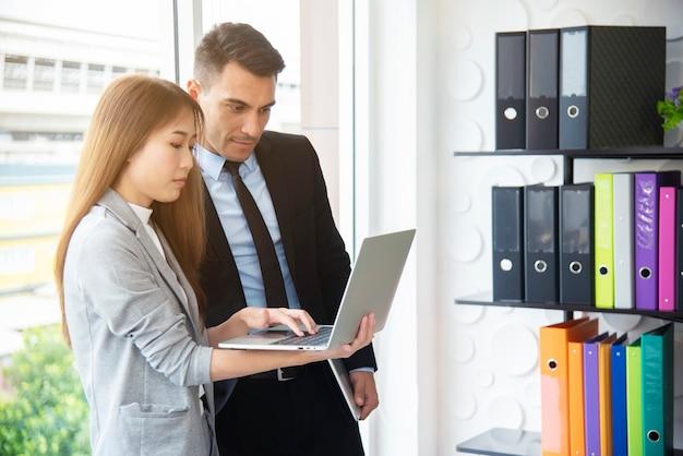 Slimme baas en secretaresse werken samen met laptop op kantoor. Premium Foto