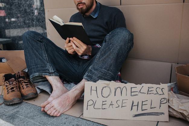 Slimme dakloze man zit op karton en leest een boek Premium Foto