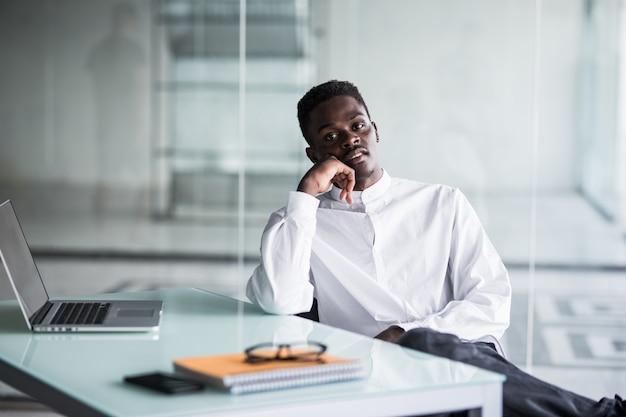 Slimme jonge zakenman die de computer in bureau bekijkt Gratis Foto
