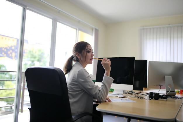 Slimme jonge zakenvrouw bemanning werken met nieuw startproject in moderne loft kantoor Premium Foto