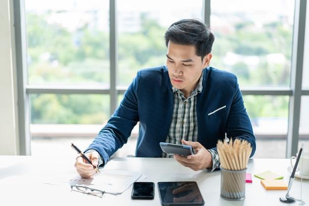 Slimme knappe aziatische zakenman die in het bureau dicht uitwerken. moderne werkplek en moderne levensstijl. Premium Foto