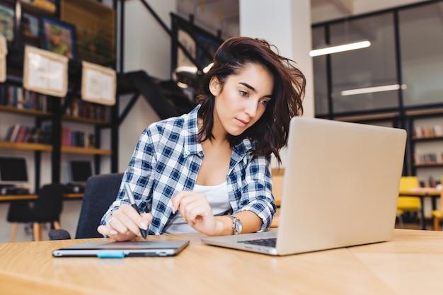 Slimme vrij jonge vrouw die met laptop op tafel in bibliotheek werkt. studeren aan de universiteit, leren, freelancer, werken, zoeken op internet, slimme student, hard werken. Gratis Foto