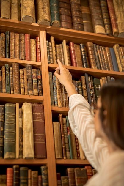 Slimme vrouwelijke student op zoek naar boek in de bibliotheek Gratis Foto