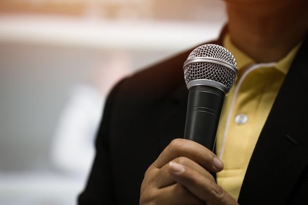 Slimme zakenmantoespraak en het spreken met microfoons in seminarieruimte of sprekend conferentiezaallicht met microfoon en keynote. spraak is een vocale vorm van communicatie mensen. Premium Foto