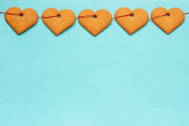 Slinger van gemberkoekjes in vorm van harten op rood lint Premium Foto