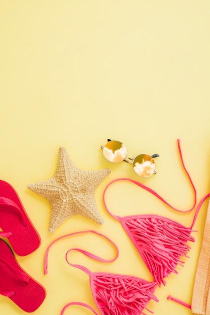 Slippers dichtbij zeester en zwempak met zonnebril Gratis Foto