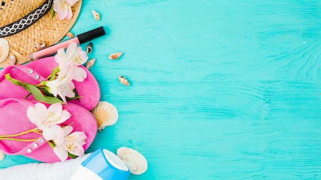 Slippers in de buurt van hoed tussen bloemen met schelpen en lippenstift Gratis Foto