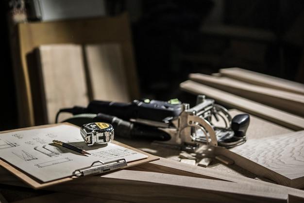 Slotter, meetlint en potlood, tekeningen op de werkbank Premium Foto