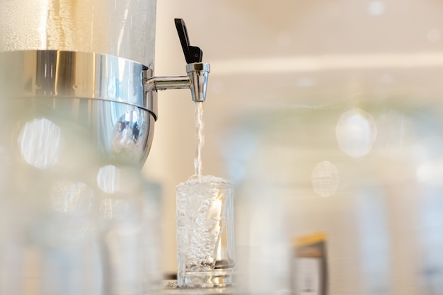 Sluit automaat koeler drinken omhoog water koude vers. waterdruppels in waterglas. voorgrond vervagen. Premium Foto