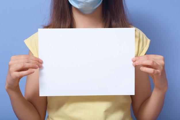 Sluit binnenbeeld van wijfje in geel t-shirt en gezichtsmasker, houdend blad van document voor tekst, overbrengend bericht, copyspace voor reclame, informatiezone. mensen en logo concept Premium Foto