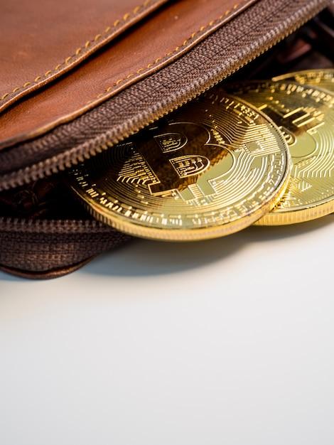 Sluit bitcoin gouden muntstukken met portefeuille op de witte achtergrond omhoog. virtueel cryptocurrency-concept. Premium Foto