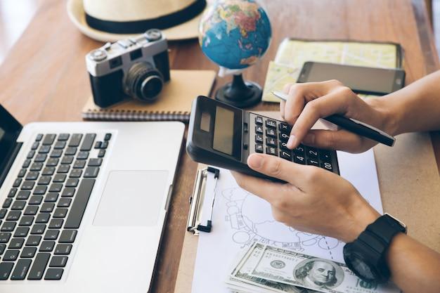 Sluit de handen van reizigers met behulp van een calculator om reiskosten te berekenen. een reis plannen, ruimte kopiëren. reis achtergrond Premium Foto