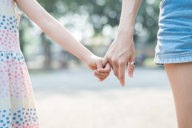 Sluit de handholding van de dochter met haar moeder, voel me getroost en aanhankelijk, gelukkige familietijd Premium Foto