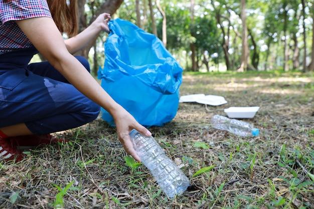 Sluit de vrijwilligershand van de vrijwilliger schoonmaken huisvuil en plastic puin op vuil bos in grote blauwe zak Premium Foto