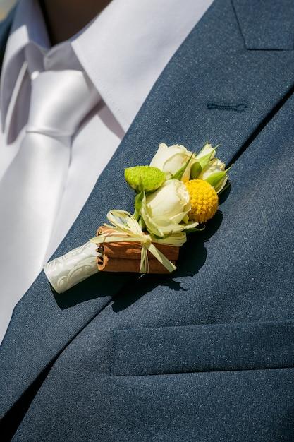 Sluit een knoopsgat van de bruidegom van beige rozen en kaneel Premium Foto