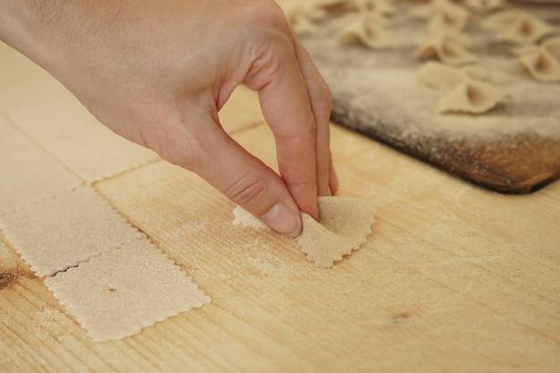 Sluit macrodetail van proces van eigengemaakte veganistische farfalle deegwaren. de kok vormt het deeg Premium Foto