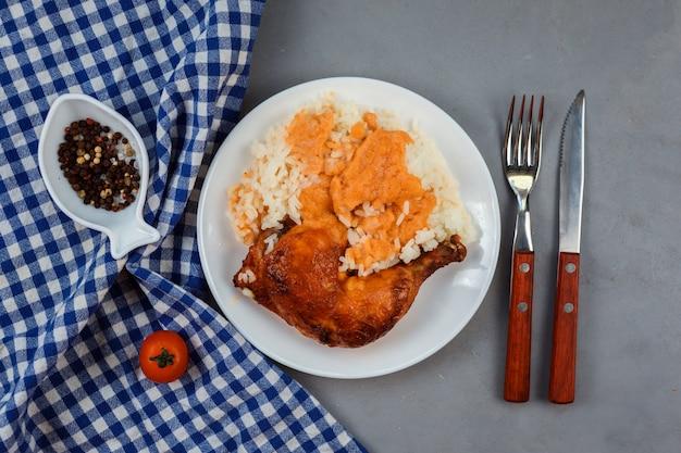 Sluit mening van het been van de kippenkerrie met rijst op de witte plaat op de grijze achtergrond omhoog wordt gediend die. blauwe servet, vork, mes, peper versieren samenstelling. Premium Foto