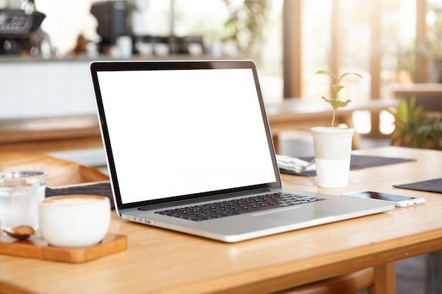 Sluit minimalistisch omhoog schot van generische laptop computer en werkende toebehoren rustend op houten lijst Gratis Foto