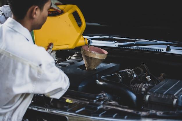 Sluit omhoog autowerktuigkundige hand die en verse olie gieten vervangen in motor van een auto bij autoreparatiegarage. automobiel onderhoud en industrie concept Gratis Foto