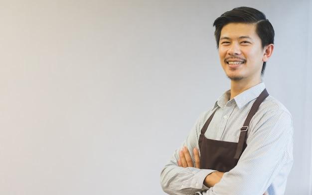 Sluit omhoog aziatisch mensen barista gekruist wapen op achtergrond, mkb-bedrijfsconcept Premium Foto