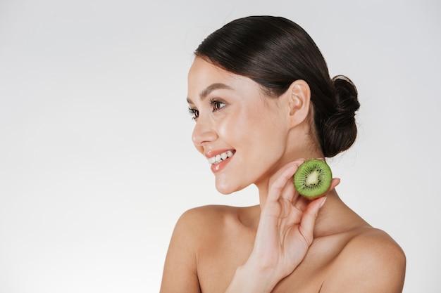 Sluit omhoog beeld van glimlachende vrouw met de gezonde verse kiwi van de huidholding en opzij kijkend, geïsoleerd over wit Gratis Foto