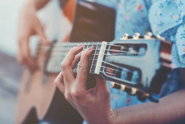 Sluit omhoog beelden van de handen die van de vrouw akoestische gitaar spelen Gratis Foto