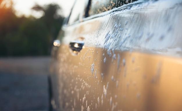 Sluit omhoog de bellen op het windscherm in een autowasserette in gouden lichte tijd. Premium Foto