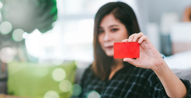 Sluit omhoog de creditcard van de vrouwenholding om thuis online te winkelen Premium Foto