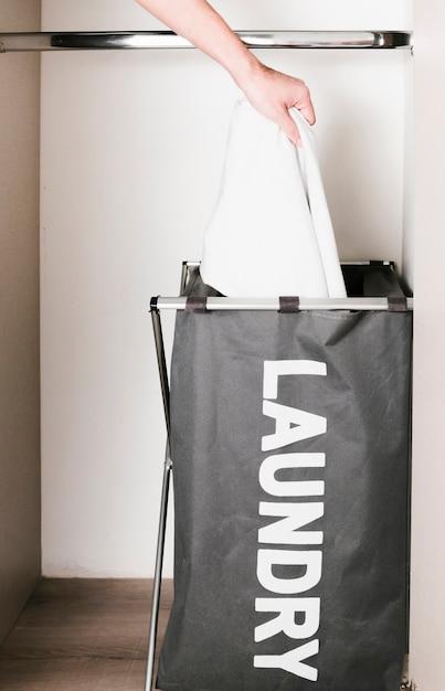Sluit omhoog de mens die kleren in wasmand zet Gratis Foto