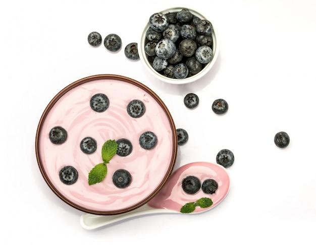 Sluit omhoog de roze romige eigengemaakte yoghurt van het bosbessenfruit met vers groen muntblad op witte achtergrond. Premium Foto