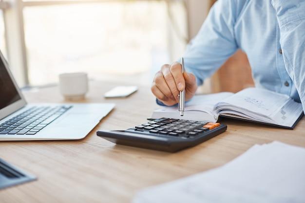 Sluit omhoog detail die van professionele ernstige accountantszitting in licht bureau, de winsten van bedrijffinanciën op calculator controleren Gratis Foto