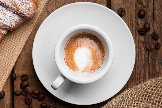 Sluit omhoog espresso met croissant en koffiezaden Gratis Foto