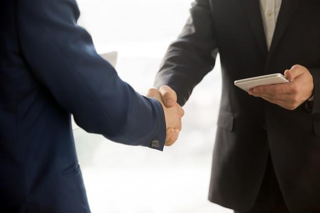 Sluit omhoog foto van het zakenlieden die van it handen schudden Gratis Foto