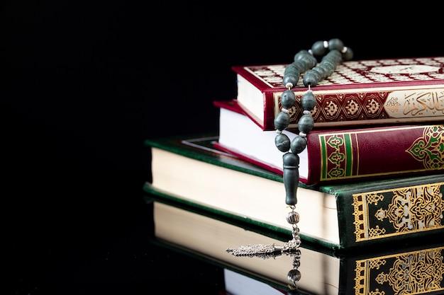 Sluit omhoog gebedparels op stapel van boeken Gratis Foto