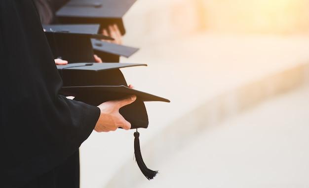Sluit omhoog gediplomeerde die een hoed houden. concept succes onderwijs op universiteit Premium Foto