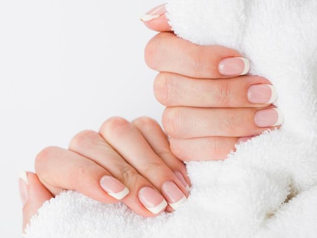 Sluit omhoog gemanicuurde handen die pluizige handdoek houden Gratis Foto