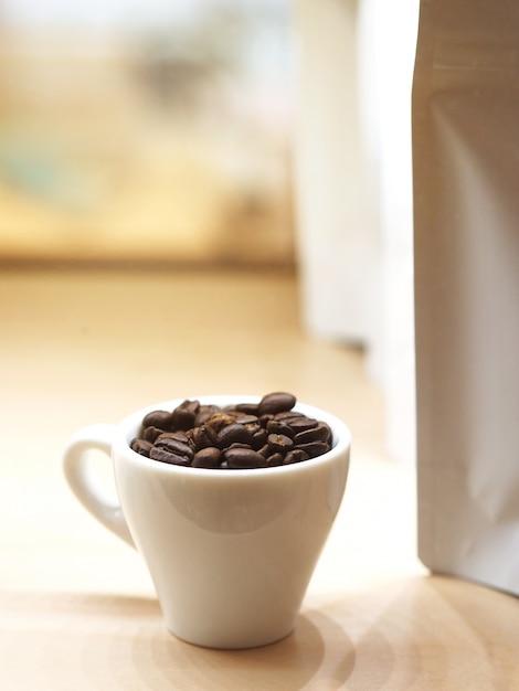 Sluit omhoog geroosterde koffieboon in witte kop Premium Foto