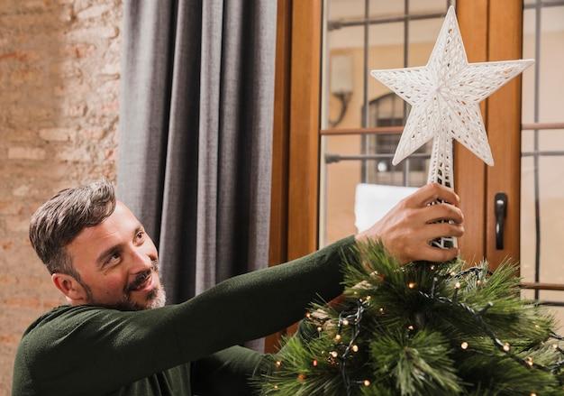 Sluit omhoog geschotene oudere mens die de ster op de boom zetten Gratis Foto
