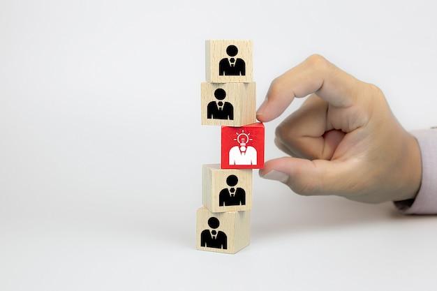 Sluit omhoog hand het kiezen van mensenpictogrammen met een gloeilamp op kubus houten stuk speelgoed blokken. Premium Foto